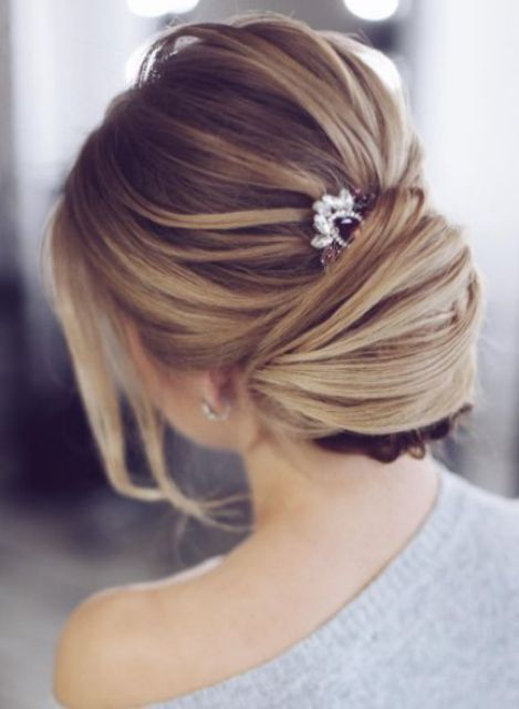 a textural low chignon hairstyle with a bump, bangs and a rhinestone hairpiece for an accent