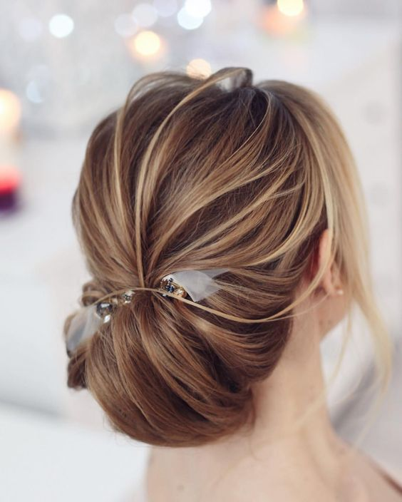 a low messy chignon hairstyle with a bump and much texture for a chic look plus a clear ribbon bow