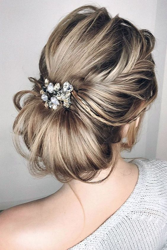a messy and textural low chignon hairstyle with a light side braid and a large rhinestone and pearl hairpiece