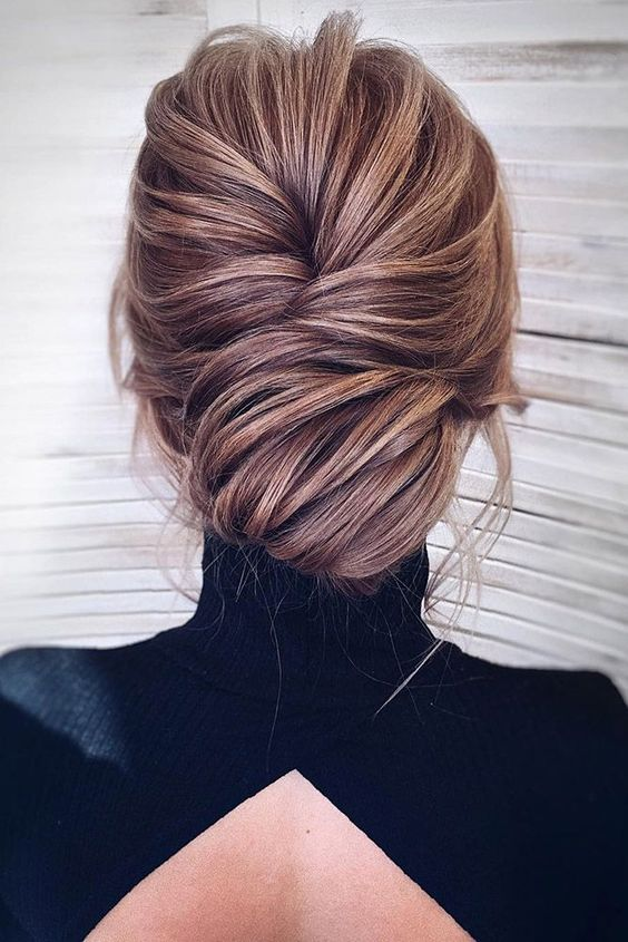 a super chic and elegant low chignon hairstyle with much volume and some bangs just wows