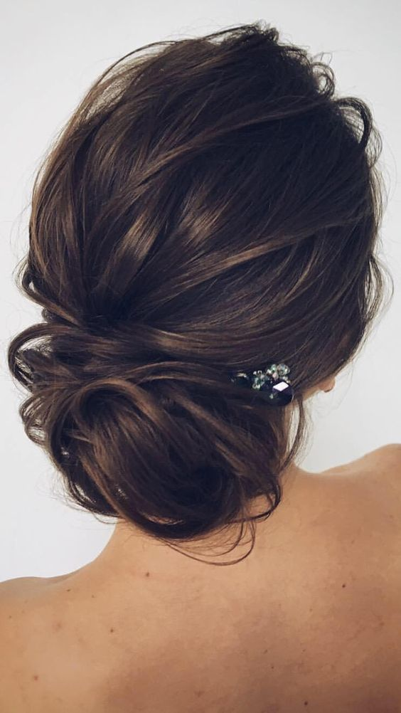 an elegant messy low updo with textures and a small rhinestone hairpiece to look effortlessly chic
