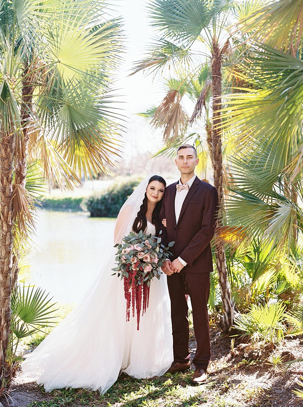 maroon groom suit and strapless wedding dress with veil