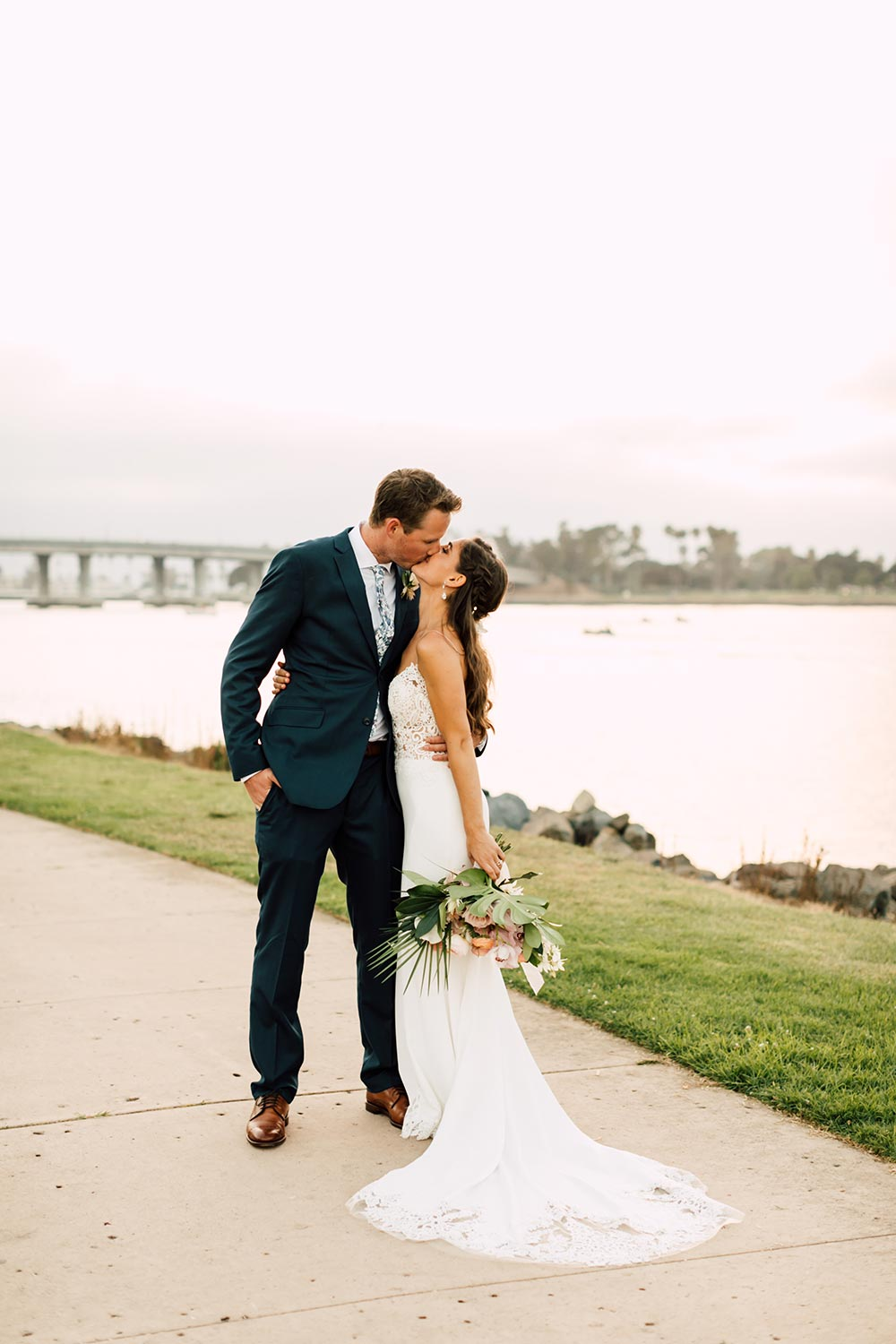 embroidered spaghetti strap wedding dress with navy groom suit and printed floral tie kiss
