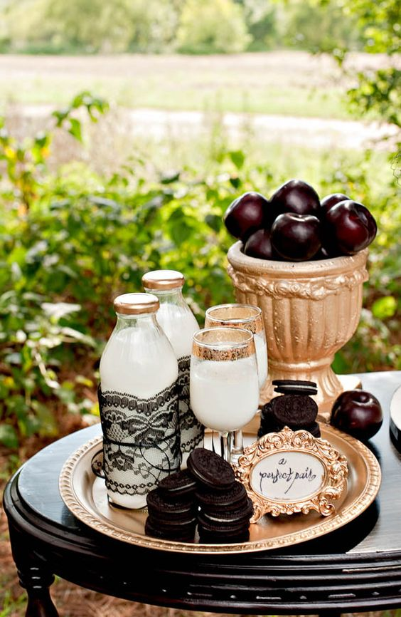 a stylish Tim Burton-inspired dessert table with milk, cookies and dark apples wows