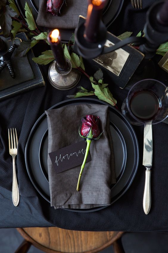 a chic black tablescape with a dried rose and fresh greenery is a great idea for a modern Halloween bridal shower