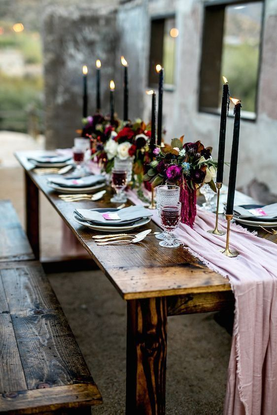 a moody tablescape with a pink table runner, black candles and gilded touches plus dark blooms