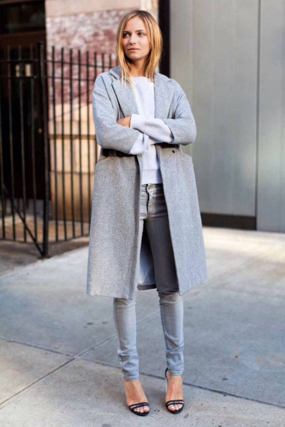 grey jeans, an off-white top, a grey coat and black heels for a simple modern look