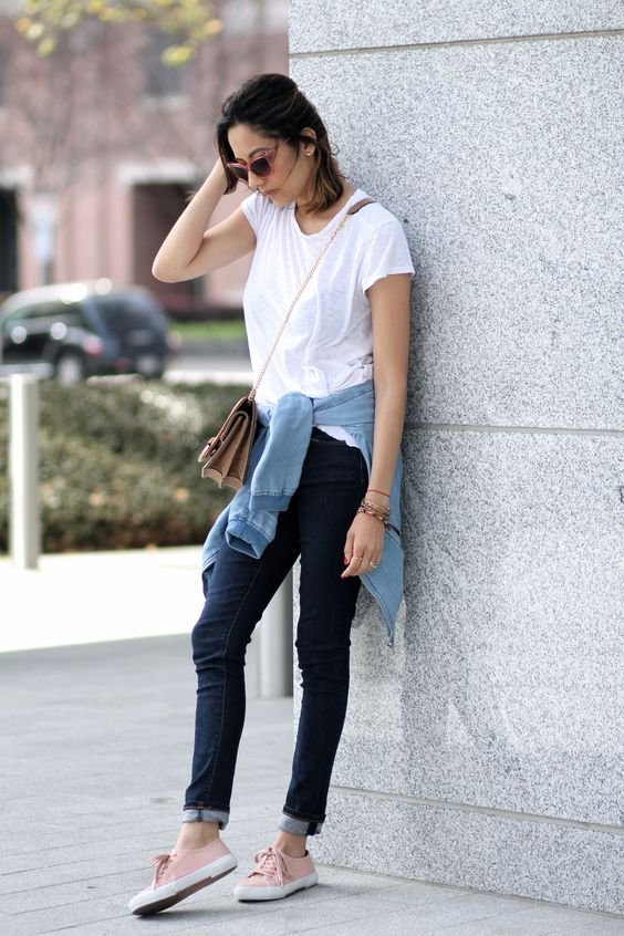 pink sneakers, navy jeans, a white tee, a tan bag, a chambray shirt