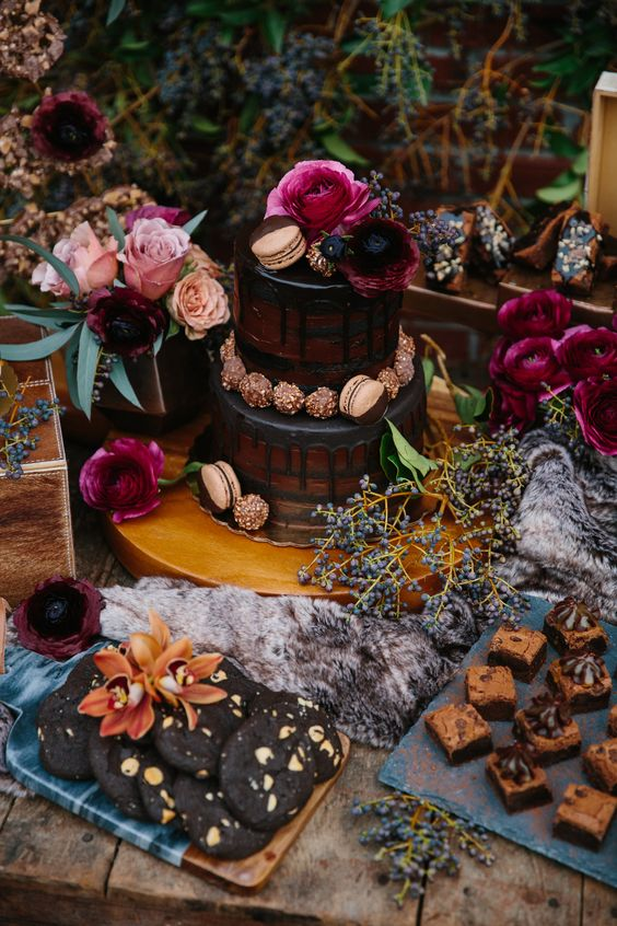 a moody dessert table with a naked cake, chocolate and cookies and fuchsia and pink blooms
