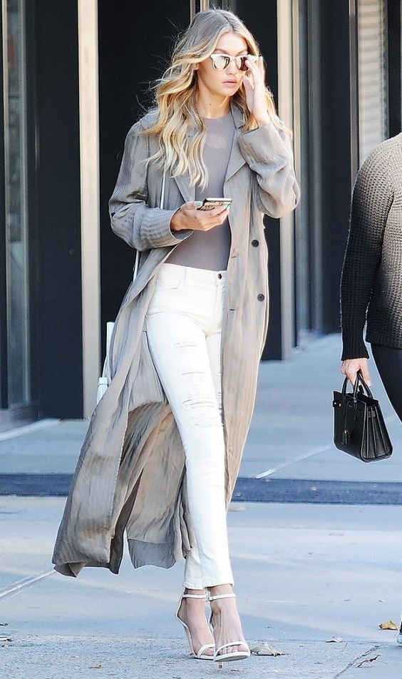 Gigi Hadid wearing white ripped skinnies, white heels, a grey top and a grey duster coat