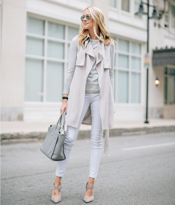 white jeans, a grey top, a neutral sleeveless coat, grey heels and a bag