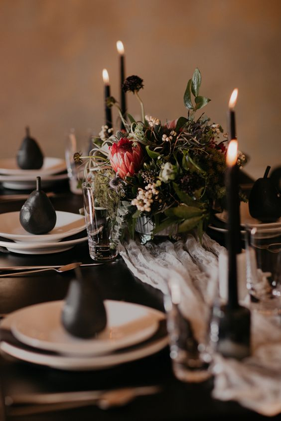 an elegant moody tablescape with a textural and herb centerpiece, black candles and pears and a black table