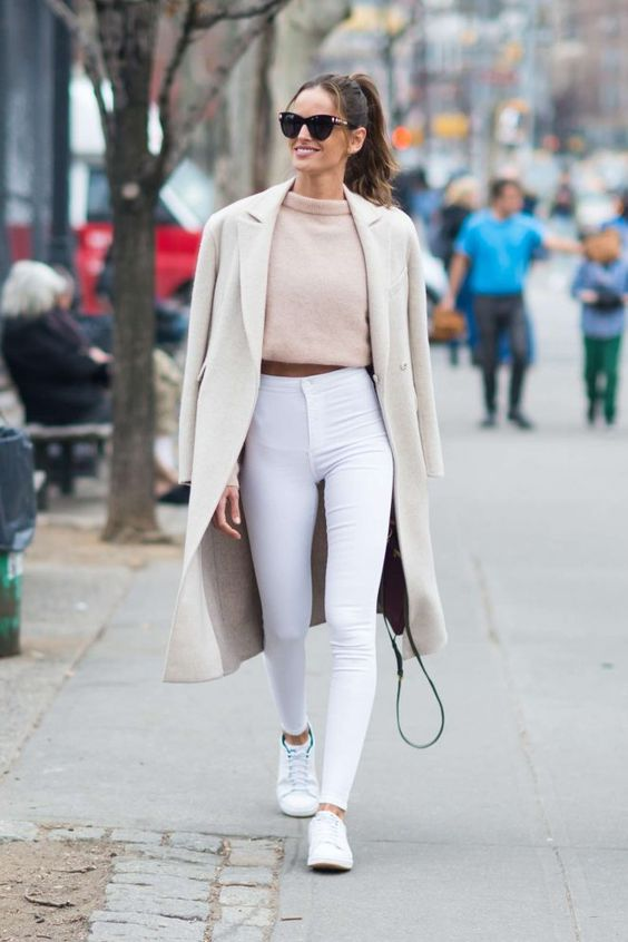 white high wasited jeans, a blush cropped sweater, white sneakers and a neutral coat