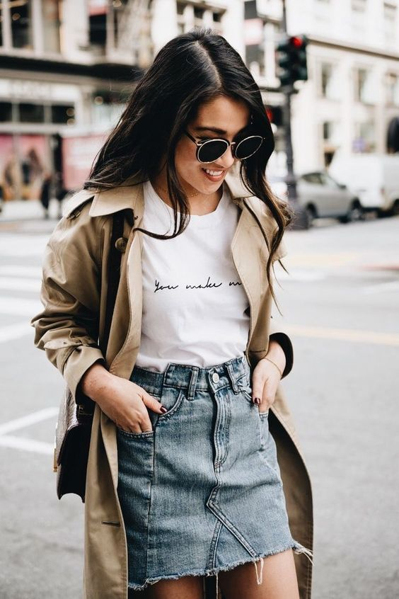 a beige trench coat, a white printed tee, a denim mini skirt with a raw hem