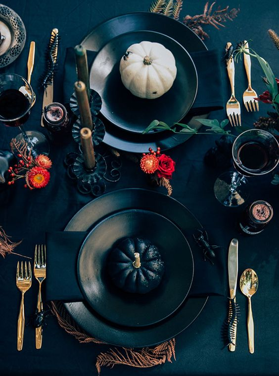 a black table setting with pumpkins, bright orange blooms, feathers and gilded touches