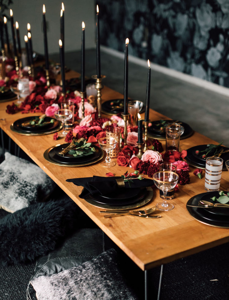 a gorgeous boho Halloween table setting with pink and burgundy blooms, black plates and candles and gilded touches