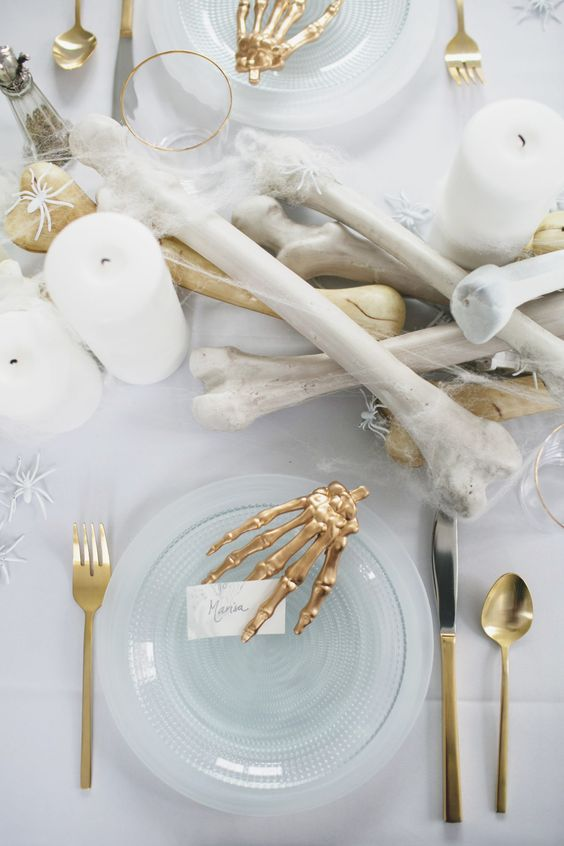 a stunning all-white tablescape with faux bones and spiders and gilded touches