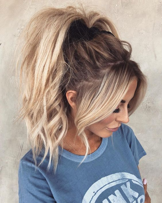 a messy and wavy very high ponytail with wavy bangs is a girlish idea to try